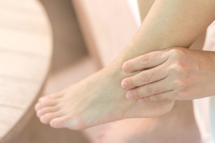 Hand holding a swollen ankle
