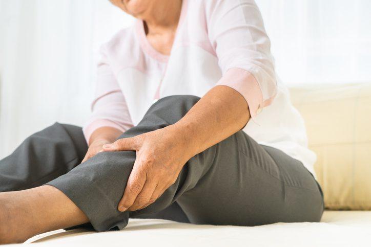 woman holding swollen leg